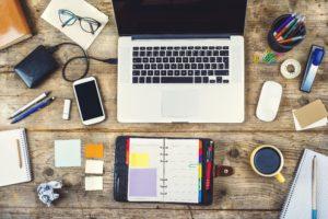 Na zdjęciu widać komputer, dysk zewnętrzny, telefon, okulary, notes, kupek z kawą oraz artykuły biurowe